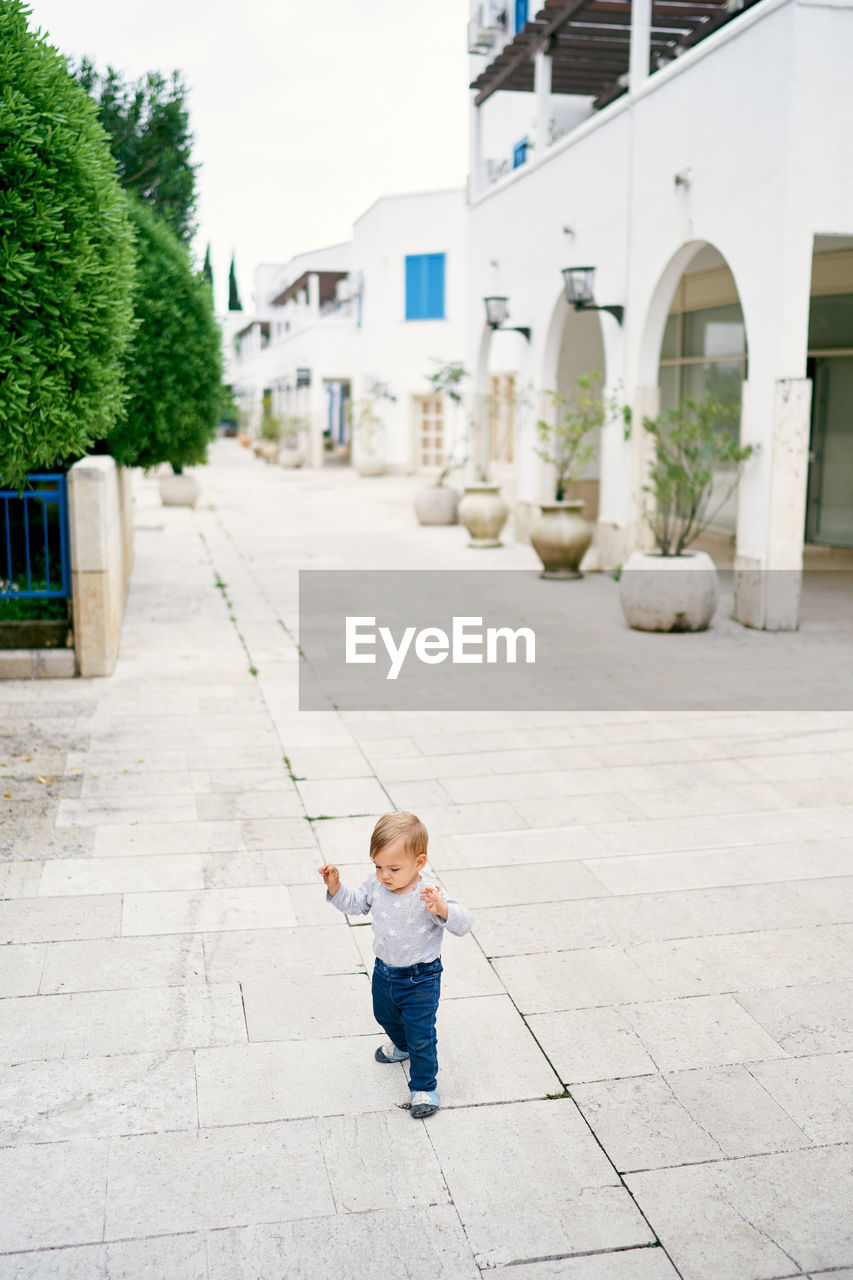 BOY STANDING ON FOOTPATH AMIDST BUILDING