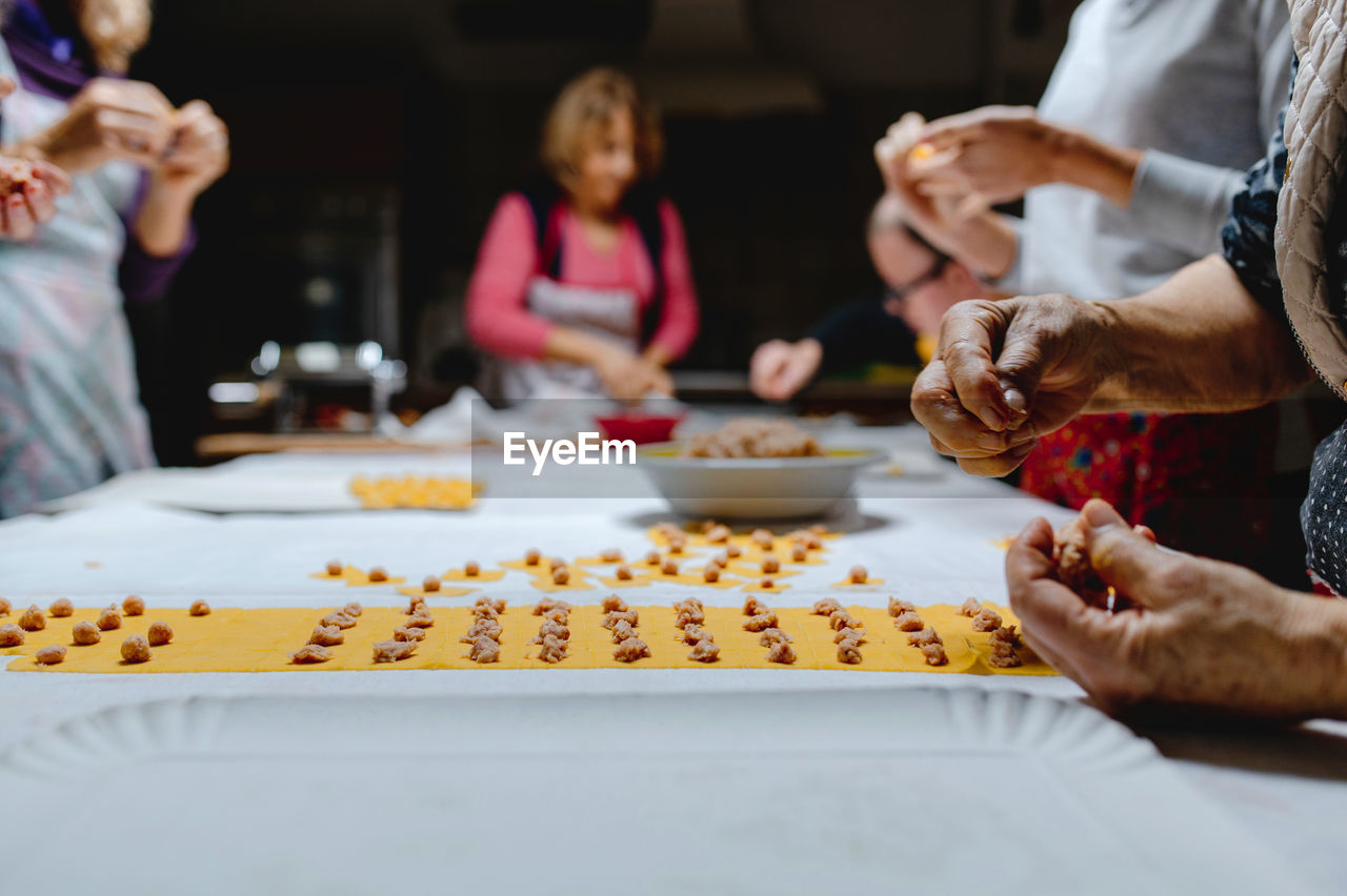 GROUP OF PEOPLE PREPARING FOOD IN KITCHEN