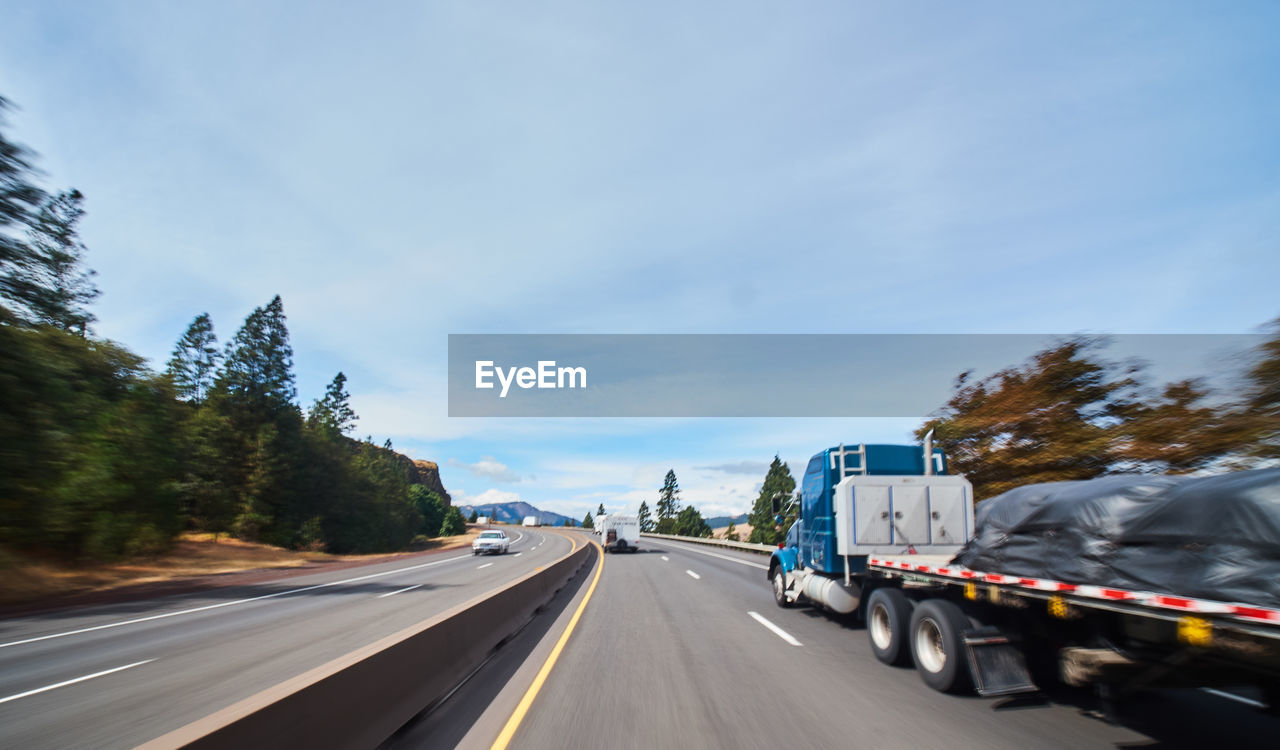 transportation, road, land vehicle, mode of transportation, motor vehicle, sky, tree, motion, the way forward, day, direction, car, road marking, symbol, truck, cloud - sky, nature, marking, sign, on the move, no people, diminishing perspective, outdoors, road trip