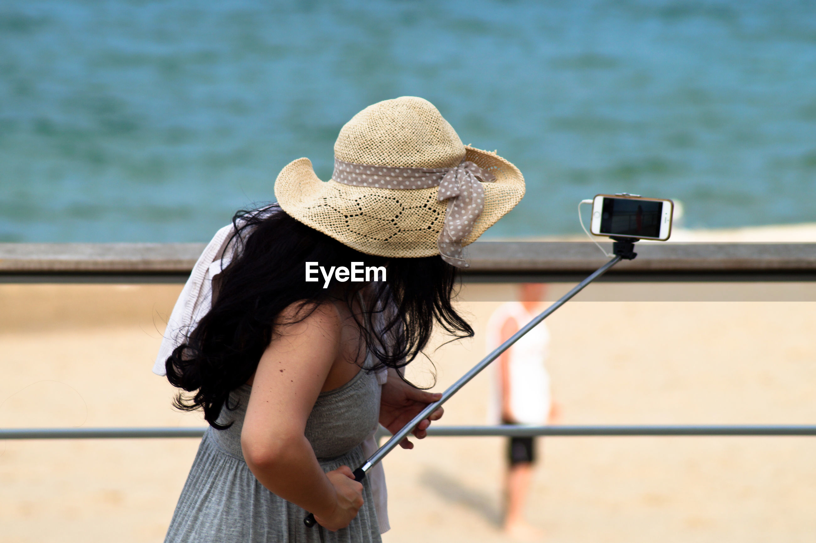 Side view of woman taking selfie with monopod at beach
