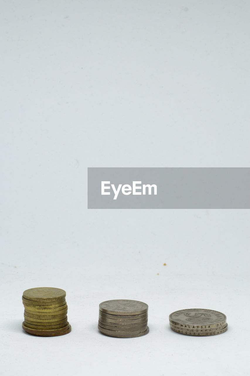 white background, studio shot, copy space, coin, still life, indoors, no people, finance, stack, business, group of objects, savings, side by side, metal, wealth, cut out, large group of objects, in a row, currency, high angle view