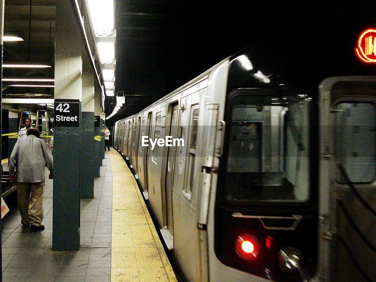 People by train at illuminated subway station platform