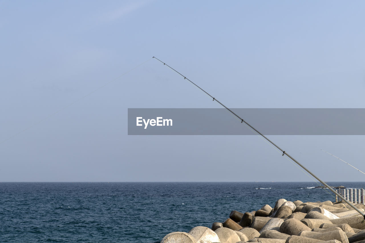 sea, water, sky, horizon, horizon over water, beauty in nature, scenics - nature, nature, tranquility, tranquil scene, day, rock, no people, solid, clear sky, idyllic, rock - object, non-urban scene, fishing rod, outdoors, groyne