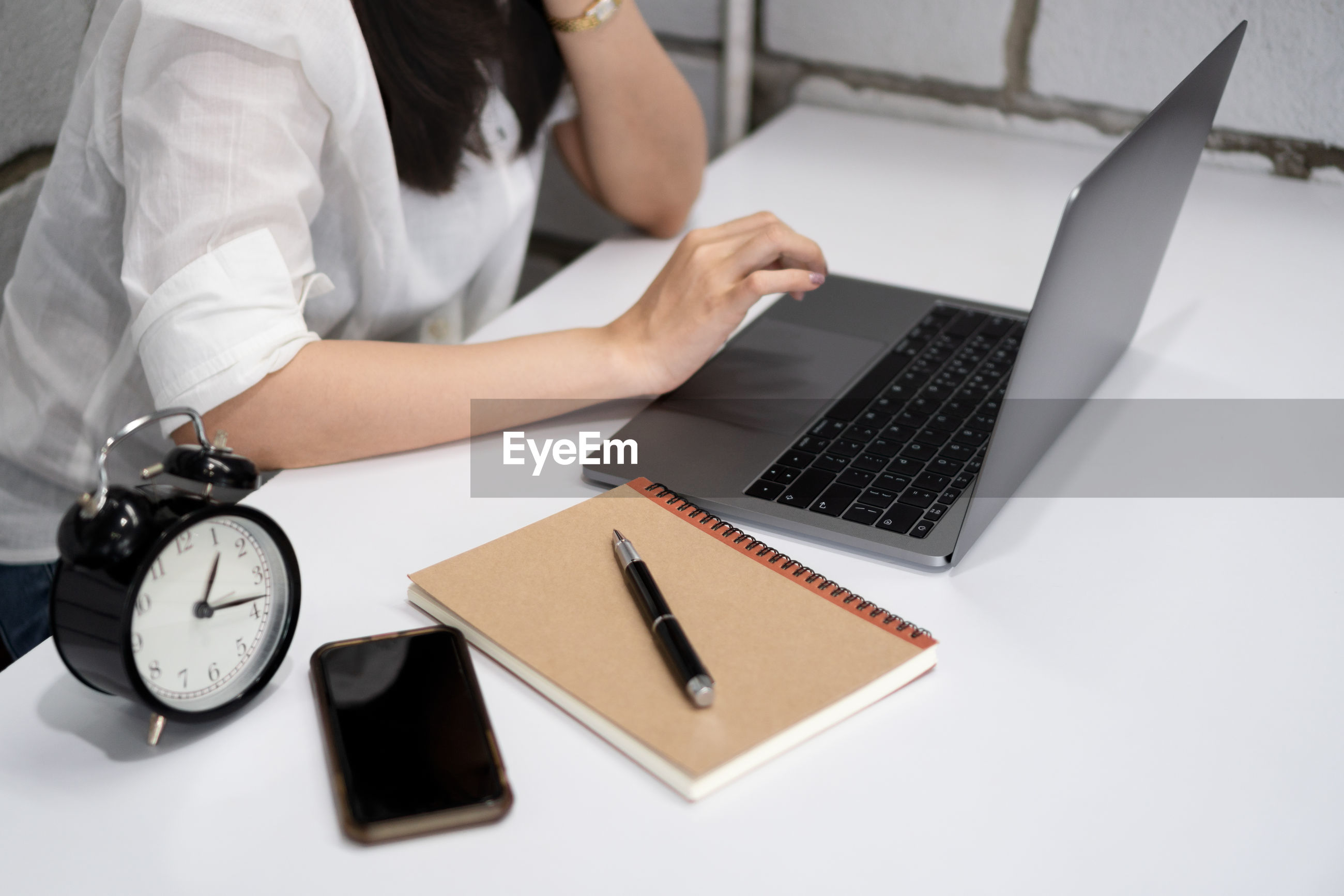 Midsection of businesswoman using laptop on desk in office