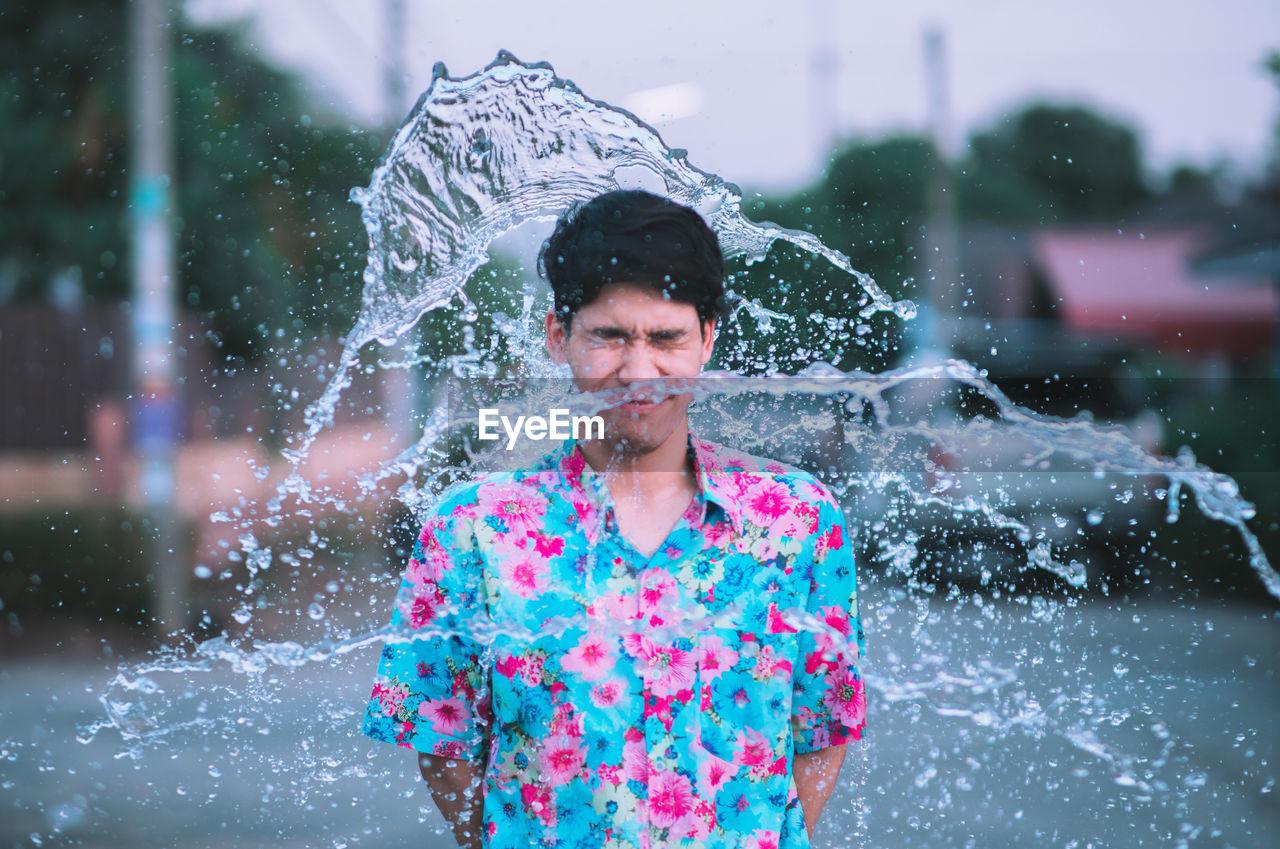 Man Standing Amidst Splashing Water