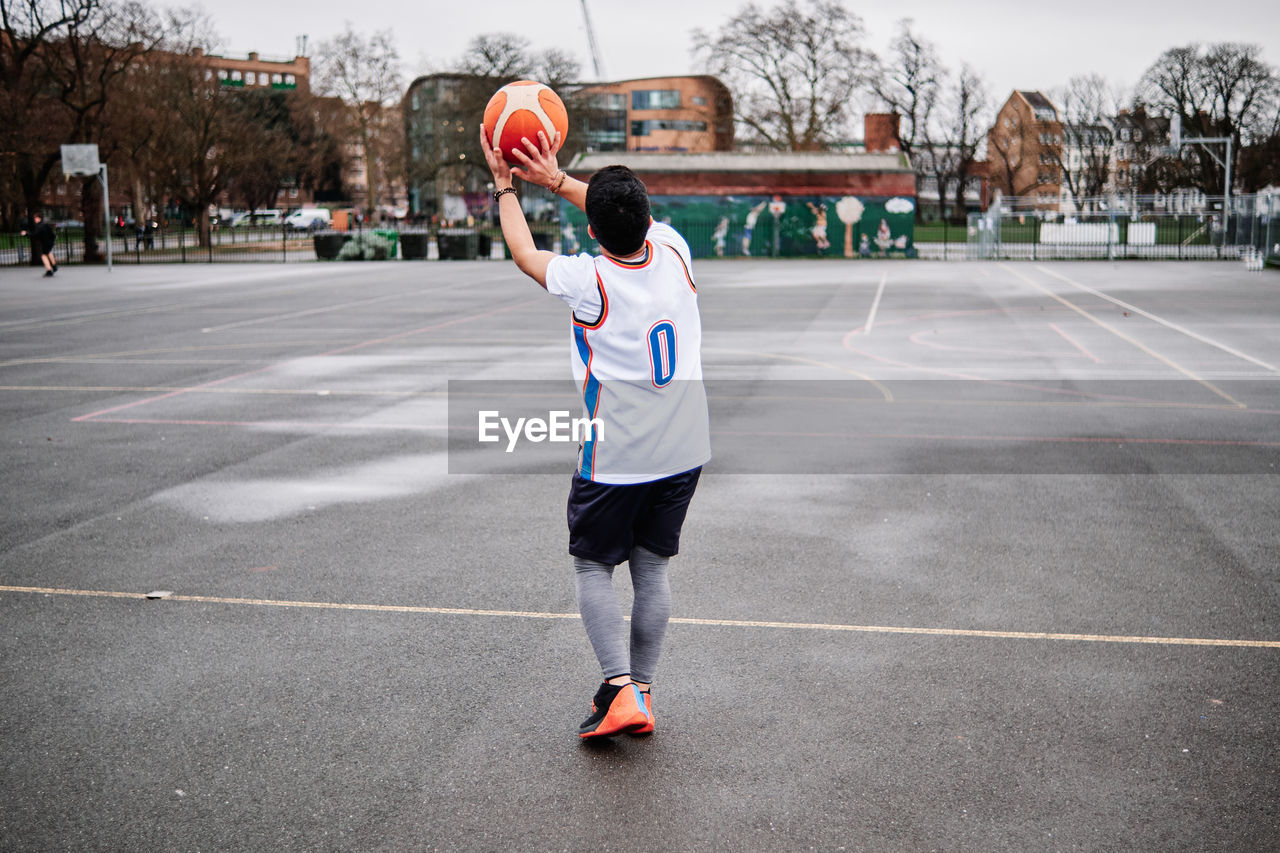 FULL LENGTH REAR VIEW OF MAN PLAYING WITH BALL IN BACKGROUND