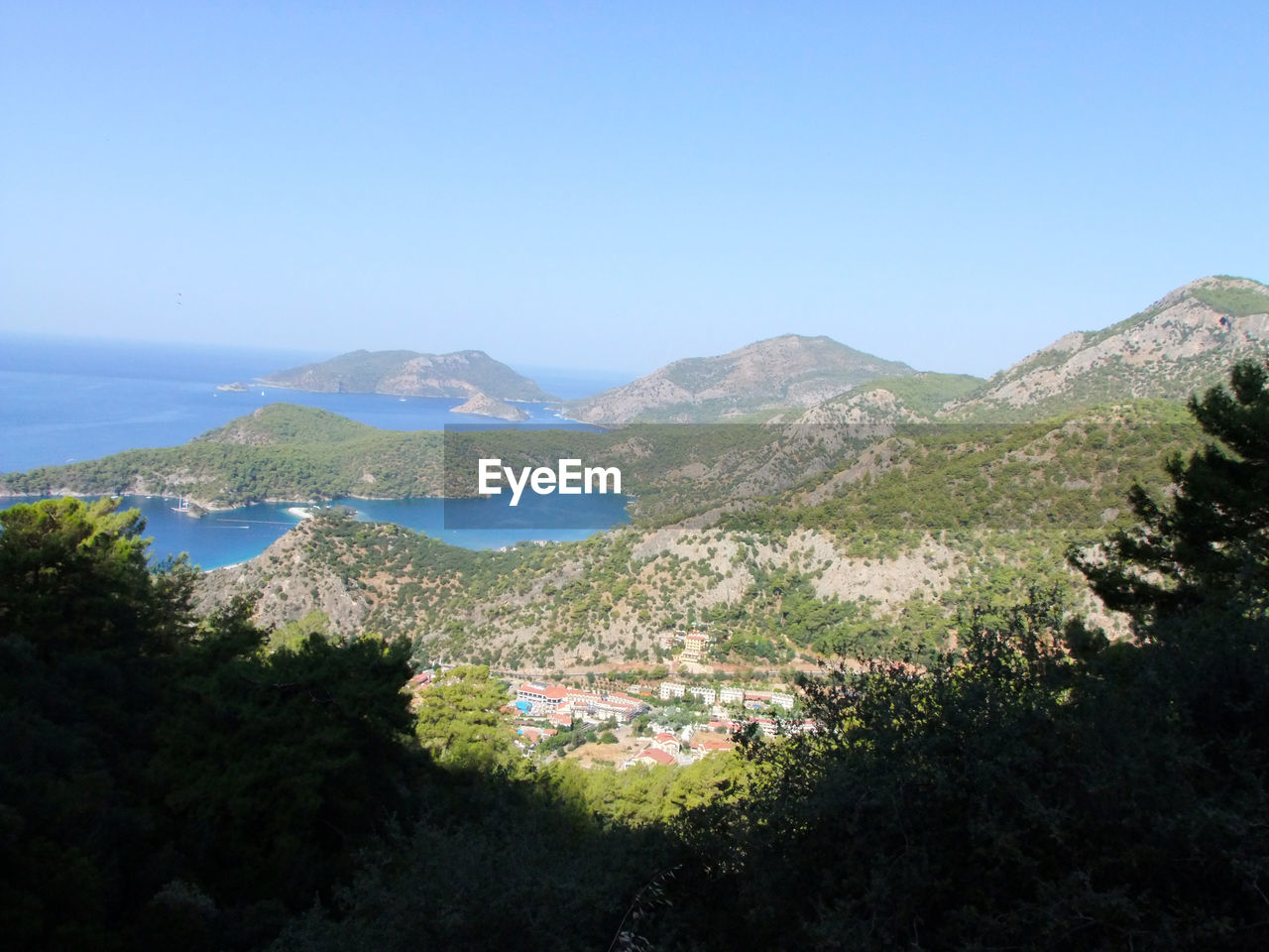 SCENIC VIEW OF MOUNTAINS AND SEA AGAINST CLEAR BLUE SKY