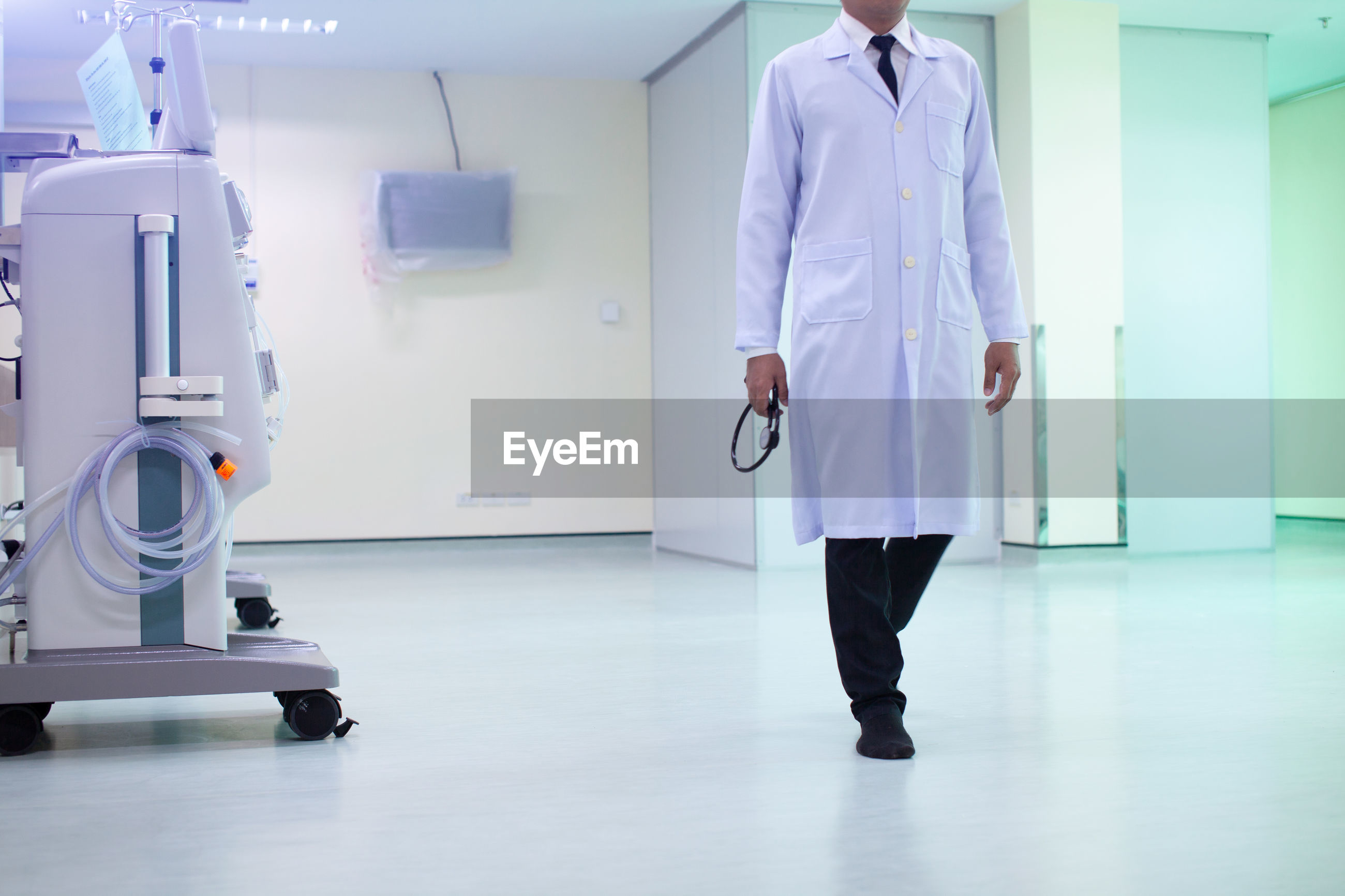 Low section of doctor walking on floor in hospital