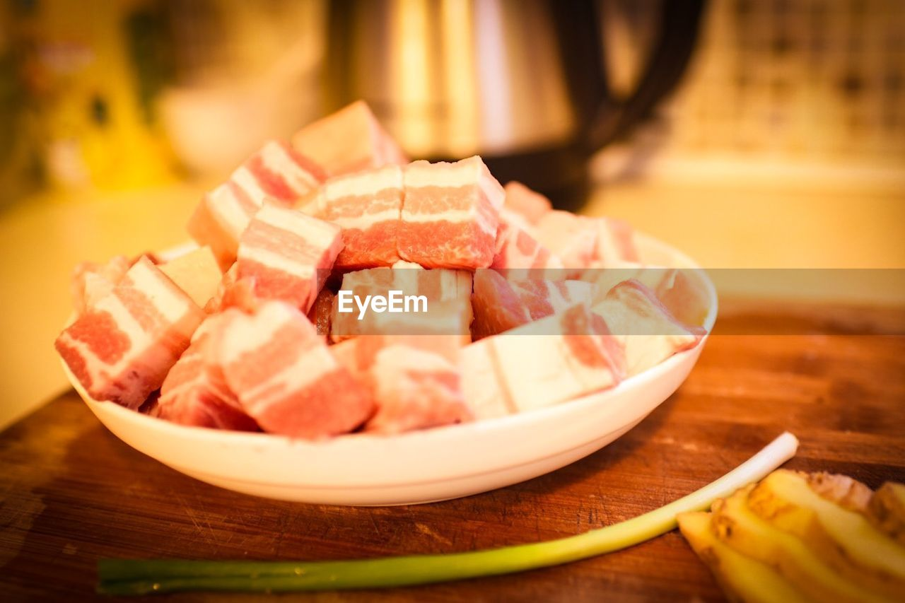 Close-up of raw pork in plate on table