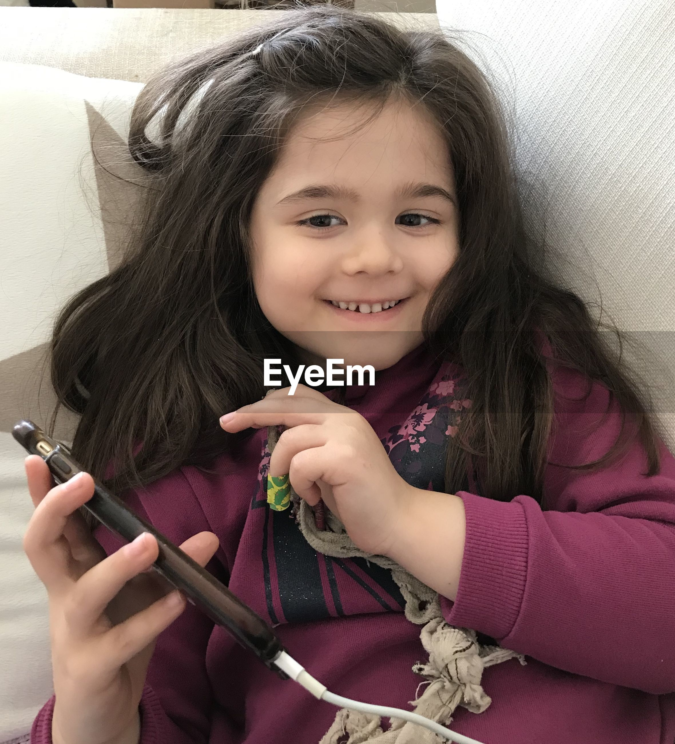 Portrait of girl smiling using smart phone while lying on sofa at home