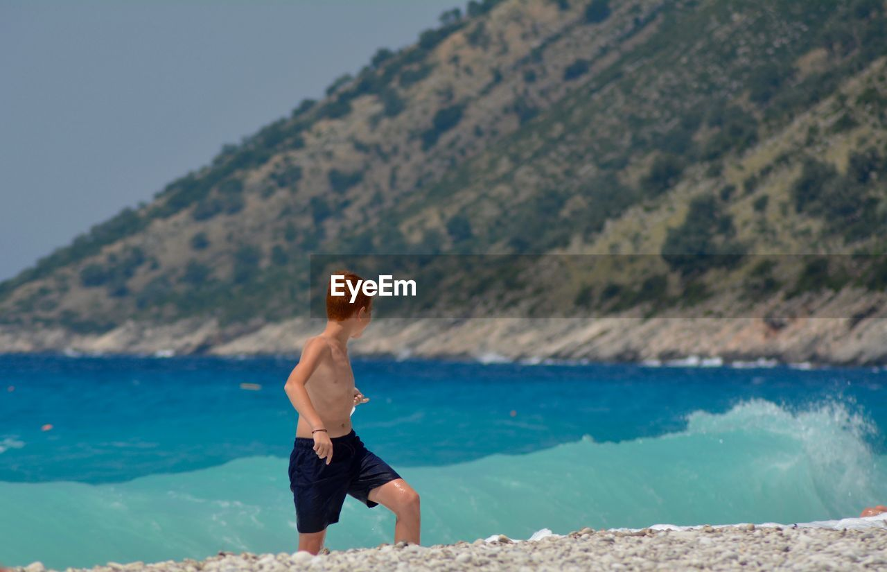 Shirtless boy running on shore at beach