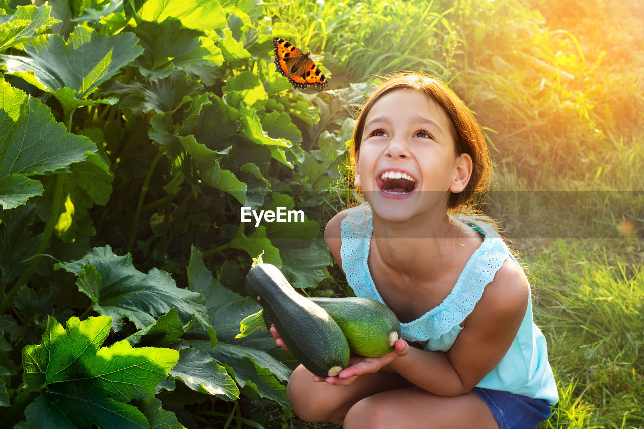 childhood, child, real people, plant, girls, smiling, lifestyles, females, one person, happiness, portrait, women, looking at camera, nature, leisure activity, emotion, growth, sitting, innocence, mouth open, outdoors