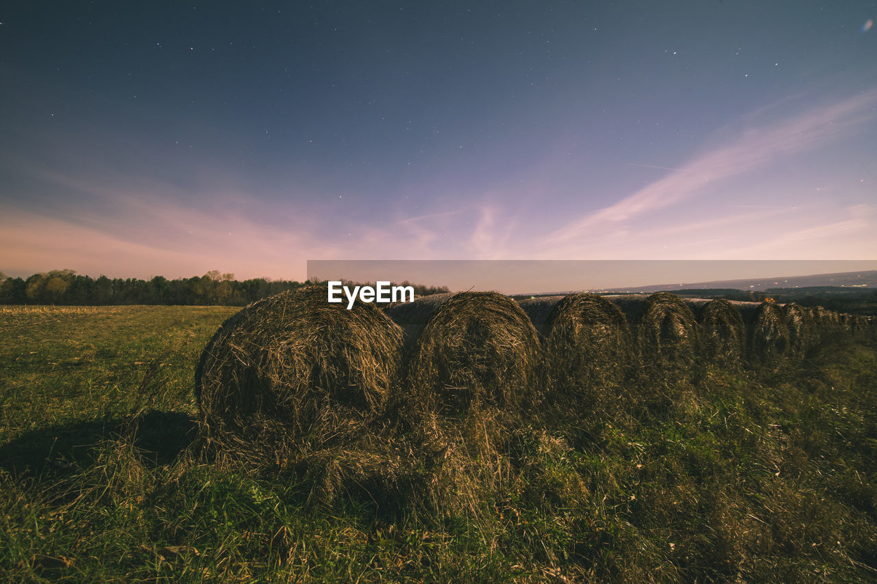 Hay Bales On Grassy Field Against Sky At Sunset