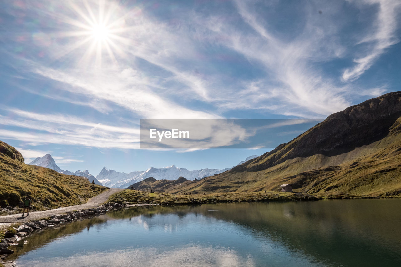 mountain, reflection, sky, nature, water, beauty in nature, scenics, tranquility, sunlight, mountain range, tranquil scene, lake, no people, waterfront, outdoors, landscape, day, scenery