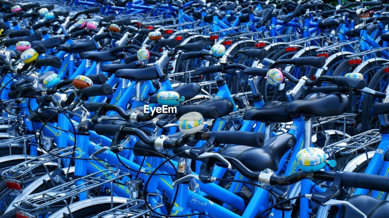blue, day, transportation, no people, large group of objects, mode of transportation, abundance, land vehicle, high angle view, technology, in a row, full frame, complexity, outdoors, stationary, nature, backgrounds, bicycle