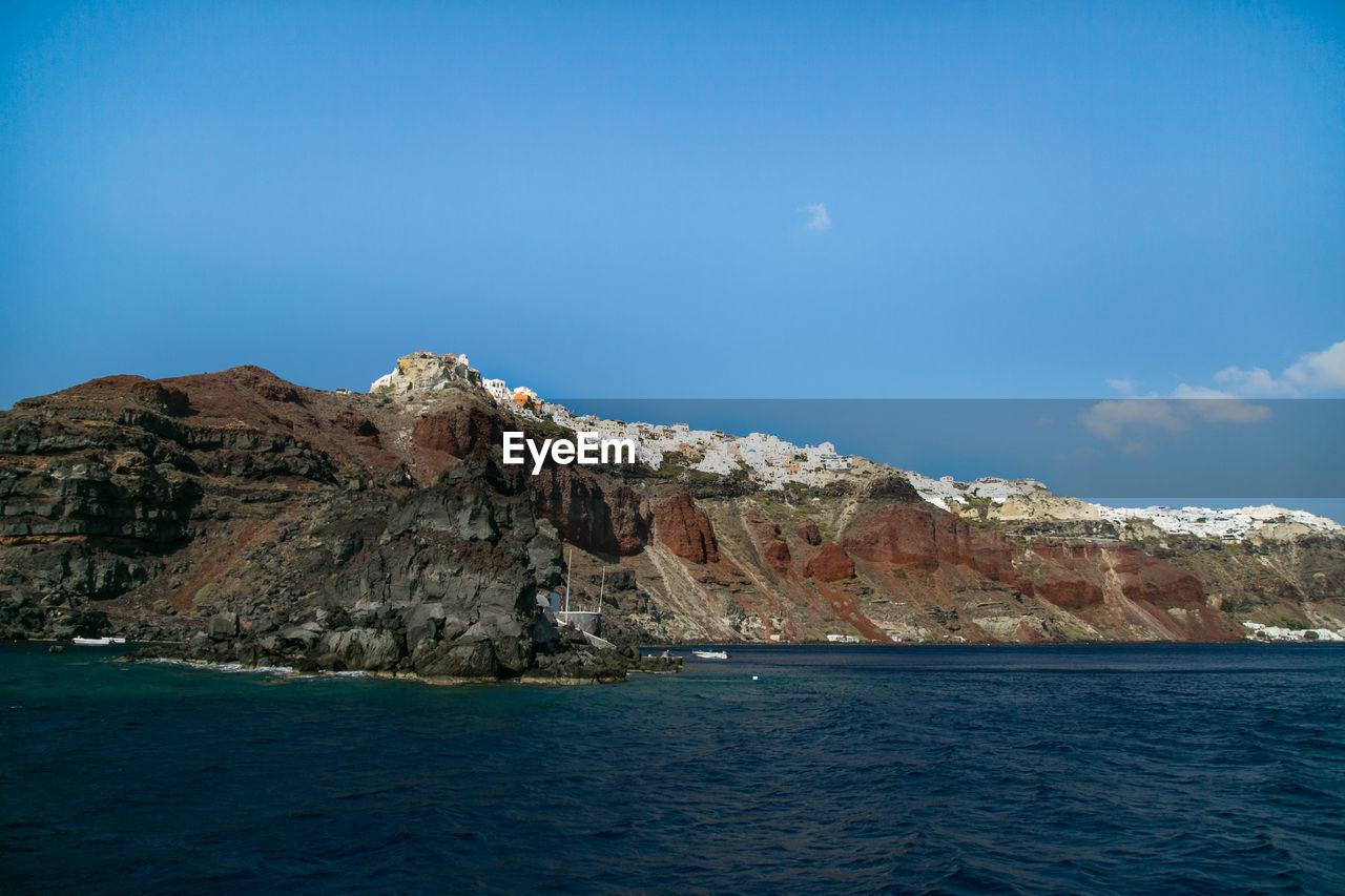 Santorini On Mountain By Sea Against Blue Sky