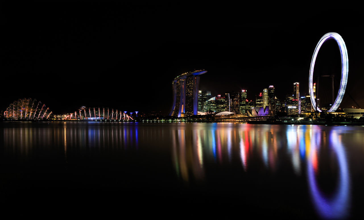 Illuminated Singapore Flyer And Skyline Reflecting On Waters Of Marina Bay