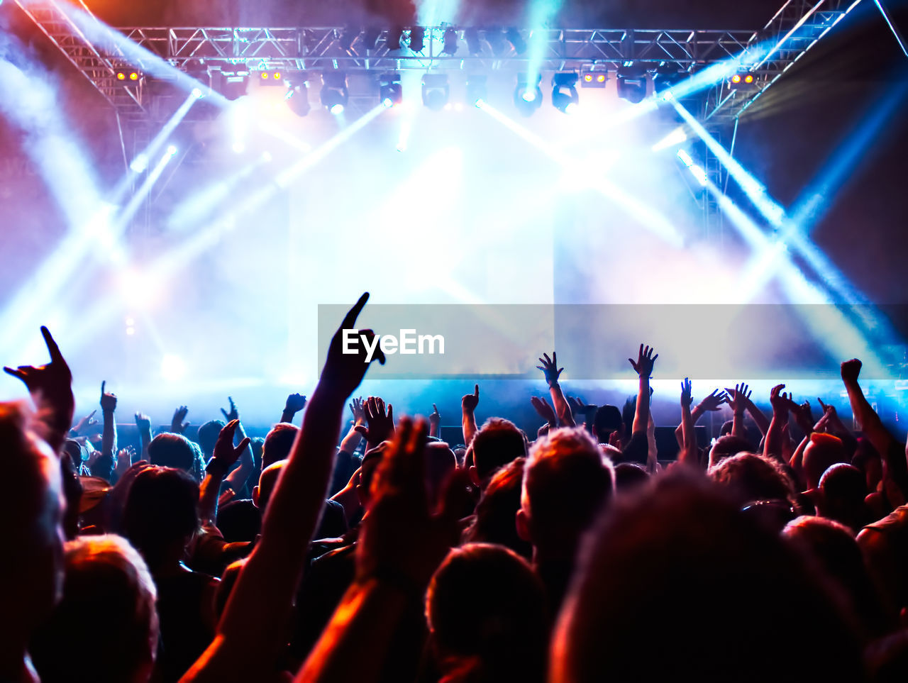 Group Of People With Arms Raised At Music Concert