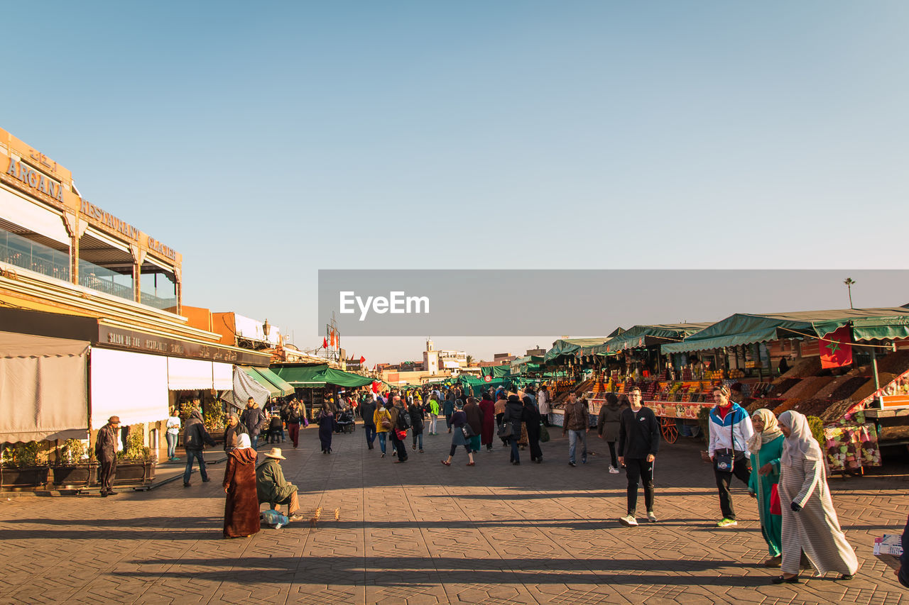 group of people, real people, large group of people, crowd, men, sky, women, architecture, built structure, adult, clear sky, lifestyles, building exterior, leisure activity, market, nature, copy space, walking, street market, outdoors