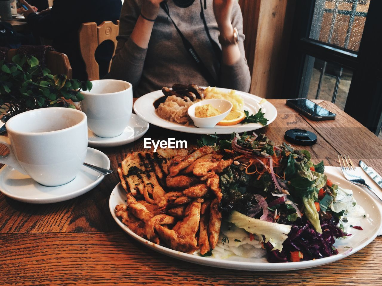 Midsection of woman with meal served on table at restaurant