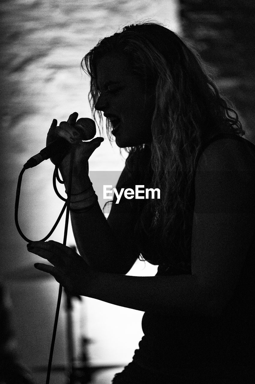 real people, one person, holding, music, leisure activity, lifestyles, microphone, skill, young adult, outdoors, musician, arts culture and entertainment, musical instrument, young women, performance, day, singing, standing, women, occupation, sky, people
