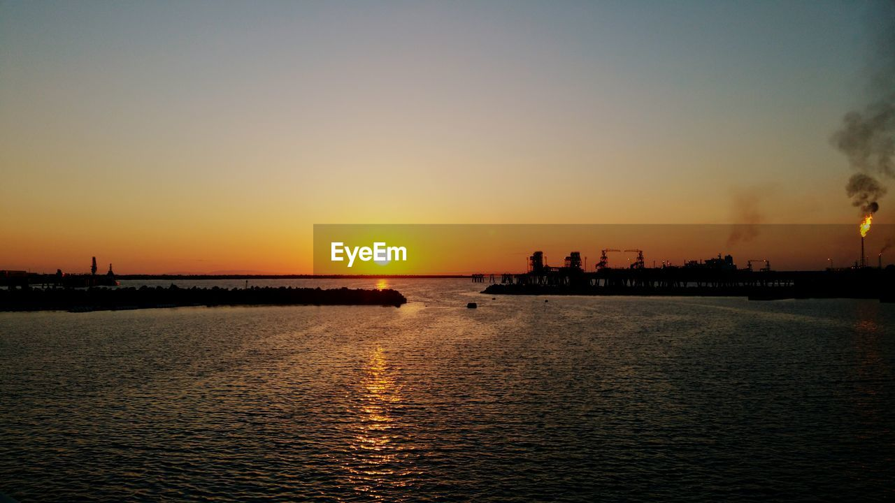 sunset, sun, silhouette, orange color, water, beauty in nature, sea, sky, nature, waterfront, scenics, sunlight, architecture, outdoors, reflection, tranquil scene, travel destinations, built structure, tranquility, building exterior, no people, dusk, city, vacations, skyscraper, cityscape, clear sky, nautical vessel, urban skyline