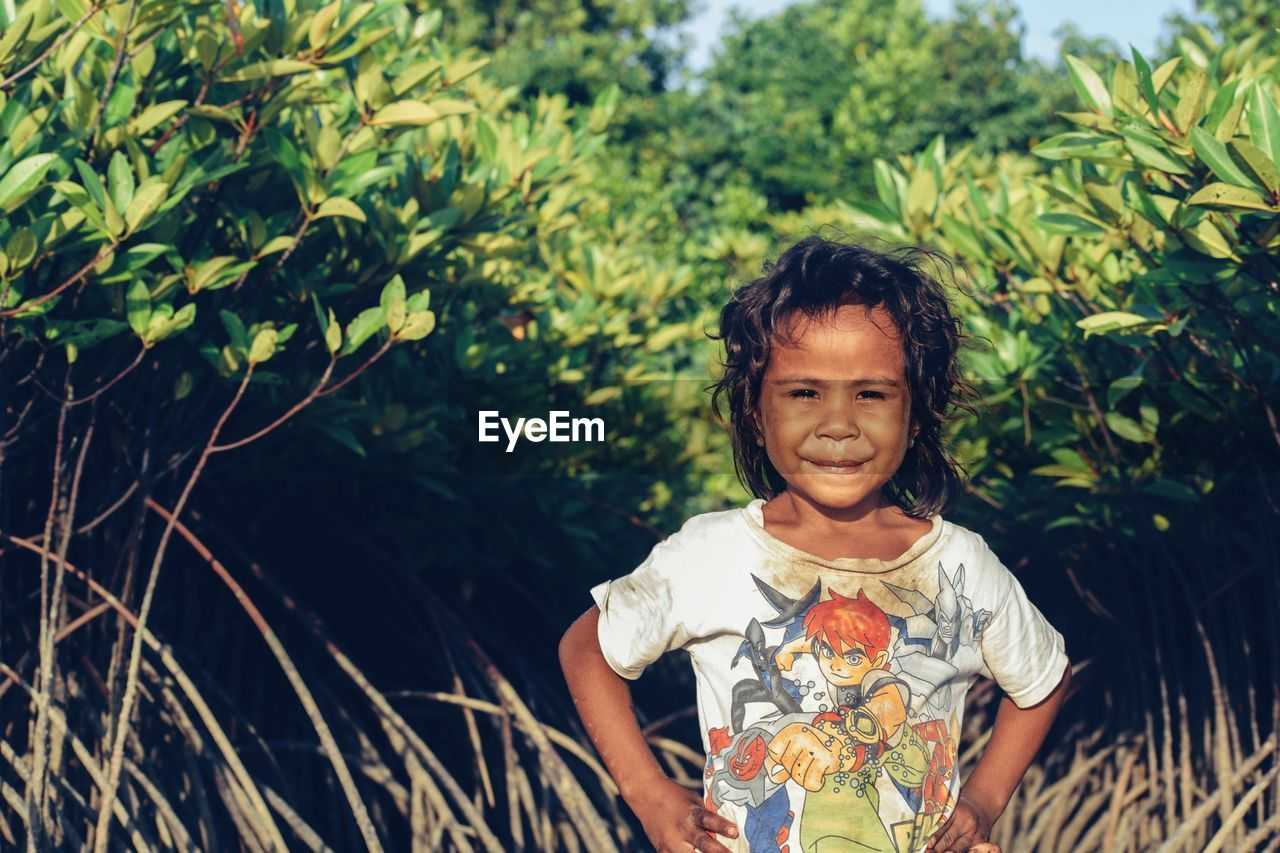 Portrait Of Girl Standing Amidst Plants