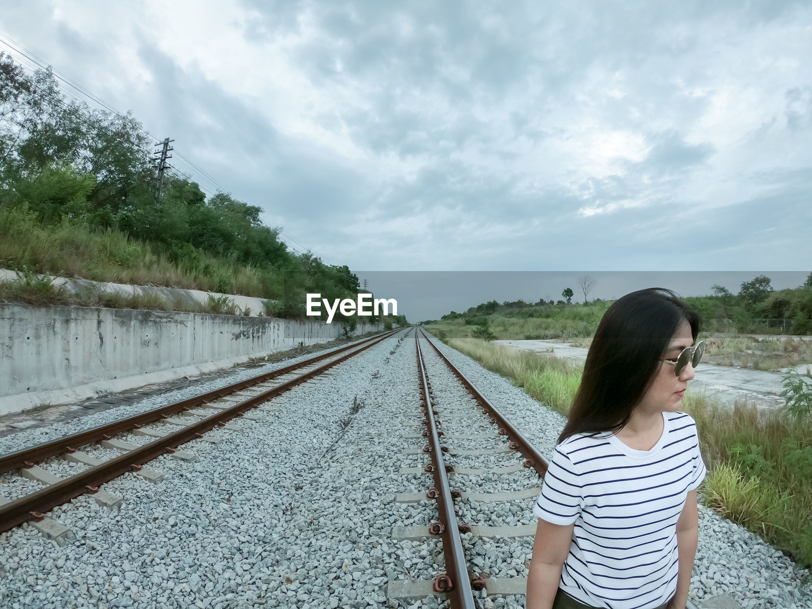 Woman looking away while standing on railroad track