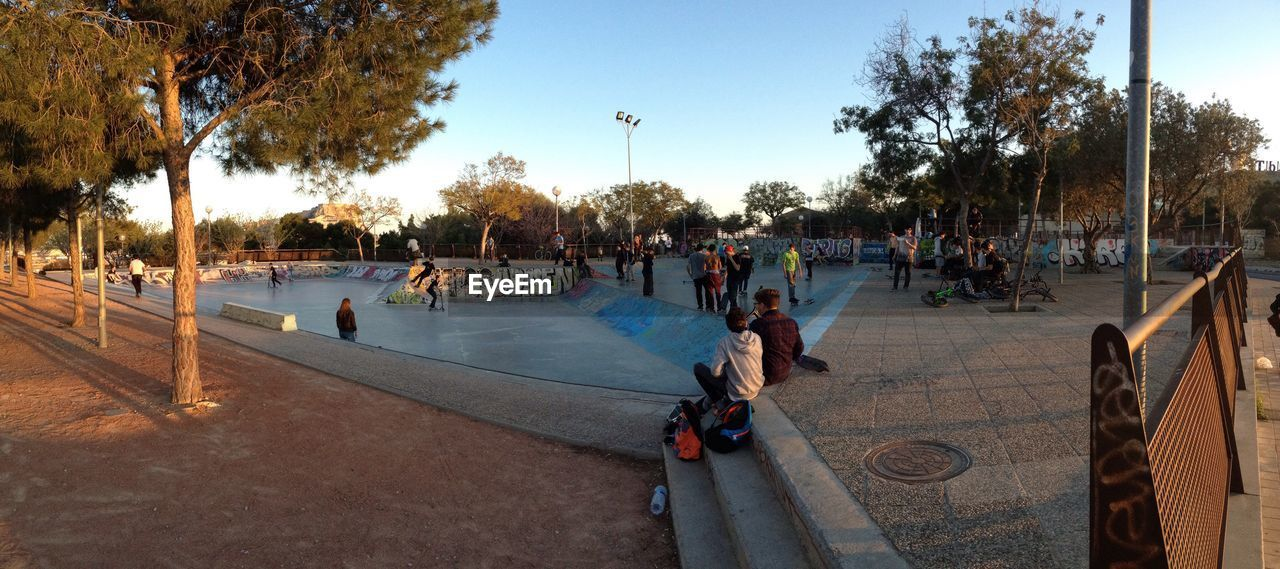 large group of people, tree, real people, leisure activity, outdoors, day, sky, lifestyles, men, playing, women, nature, skateboard park, people, adult