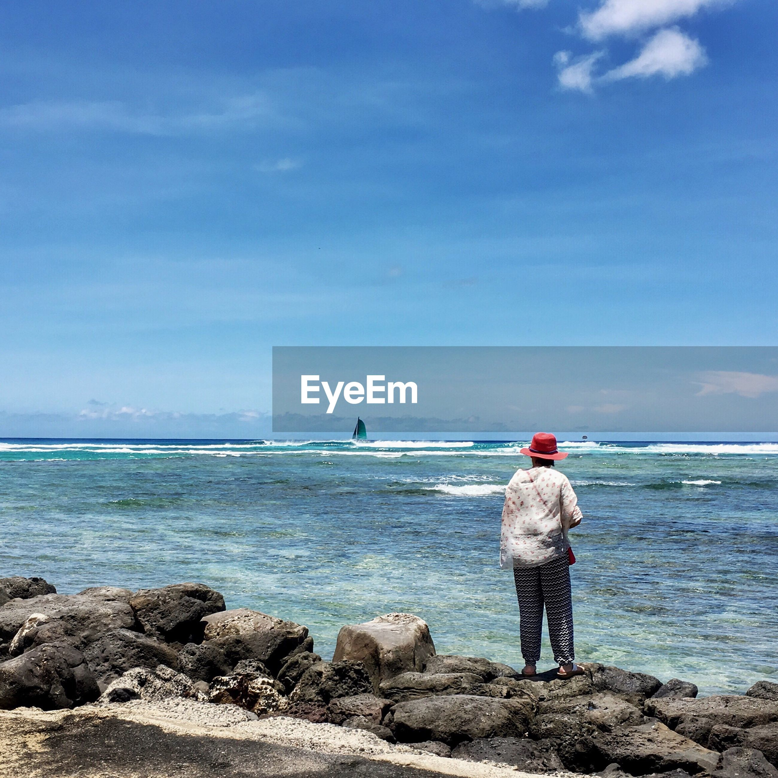Rear view of woman standing on rocky shore
