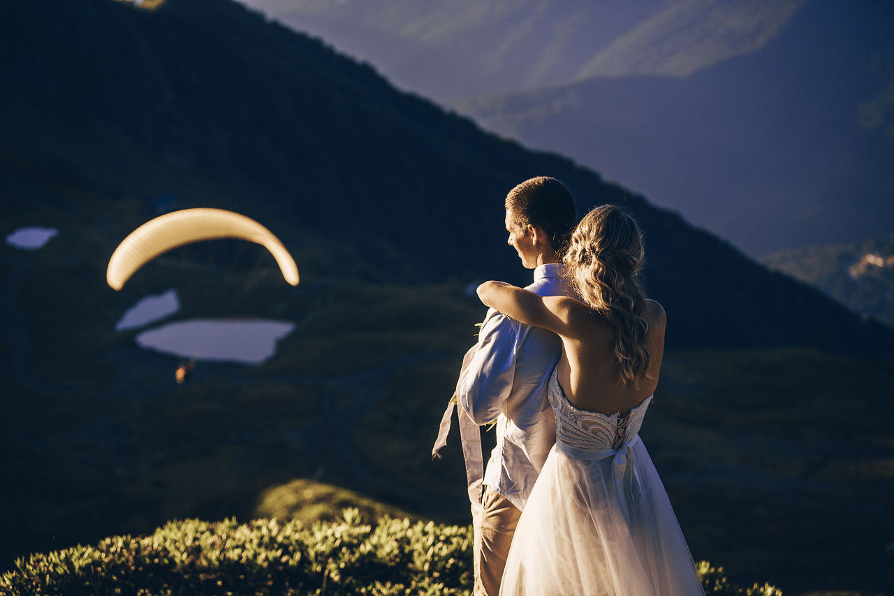 Rear view of couple standing against mountains