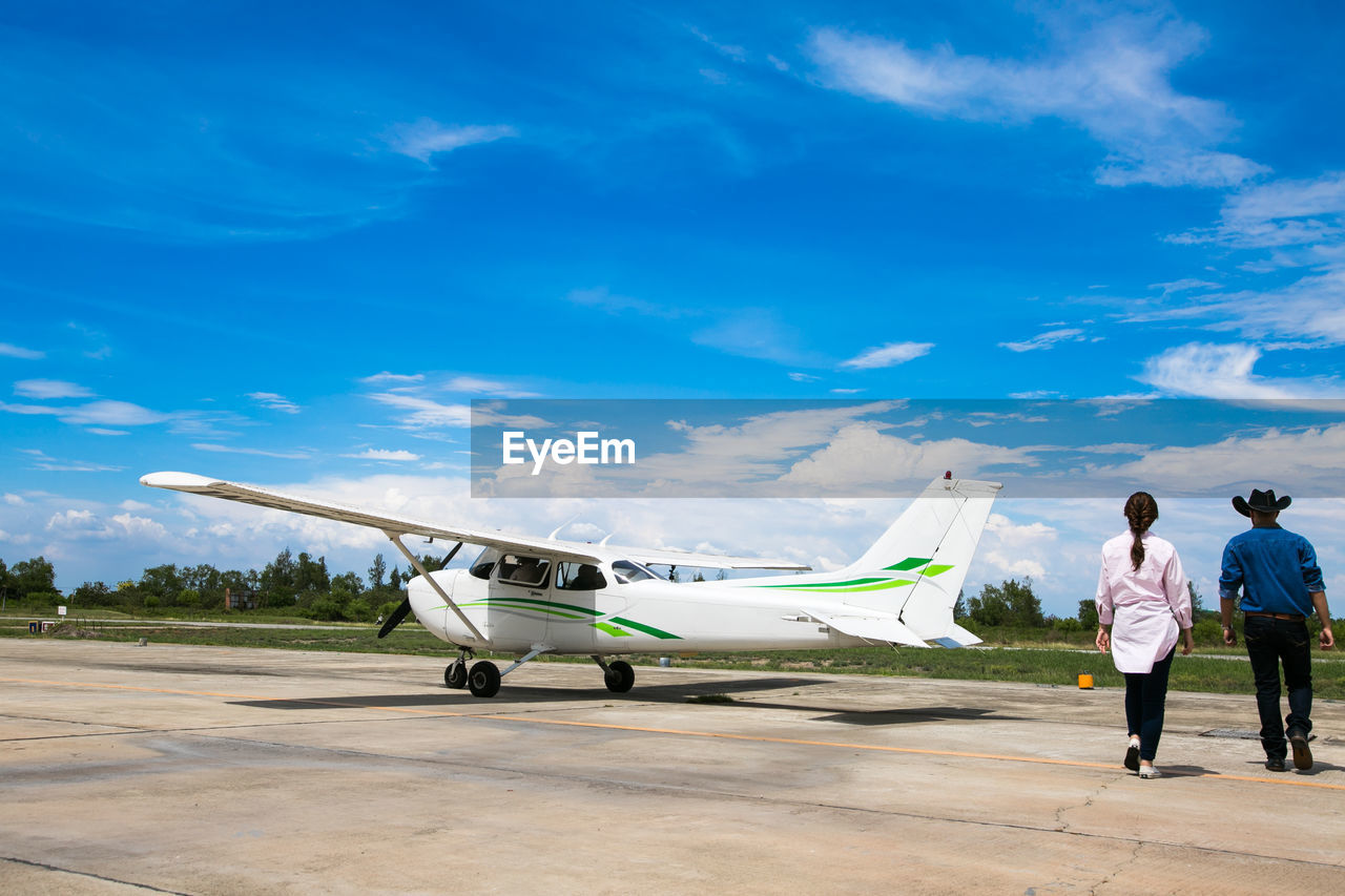 air vehicle, airplane, airport, transportation, mode of transportation, sky, rear view, men, airport runway, cloud - sky, travel, nature, real people, blue, day, people, full length, adult, lifestyles, leisure activity, private airplane, aerospace industry, corporate jet