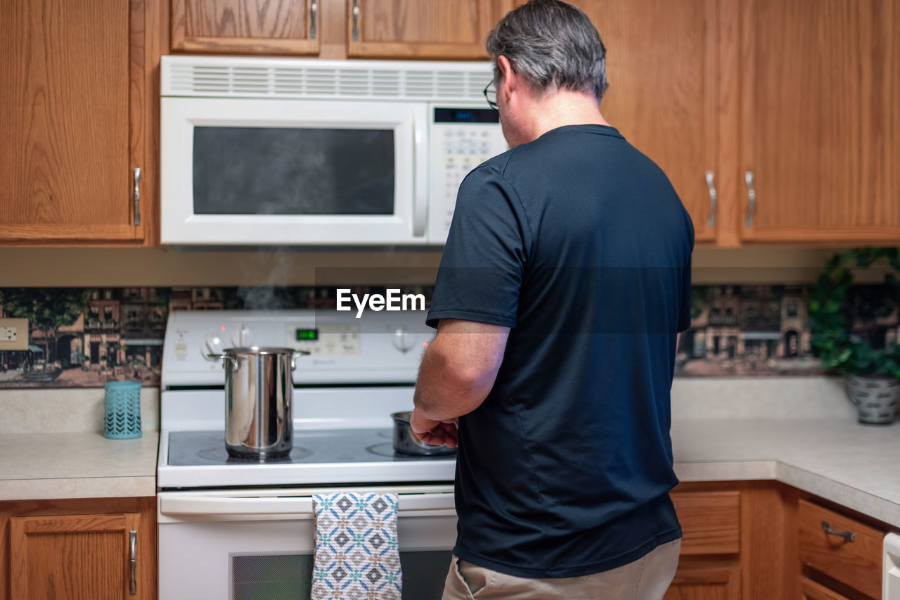 Rear view of man cooking food on stove at home