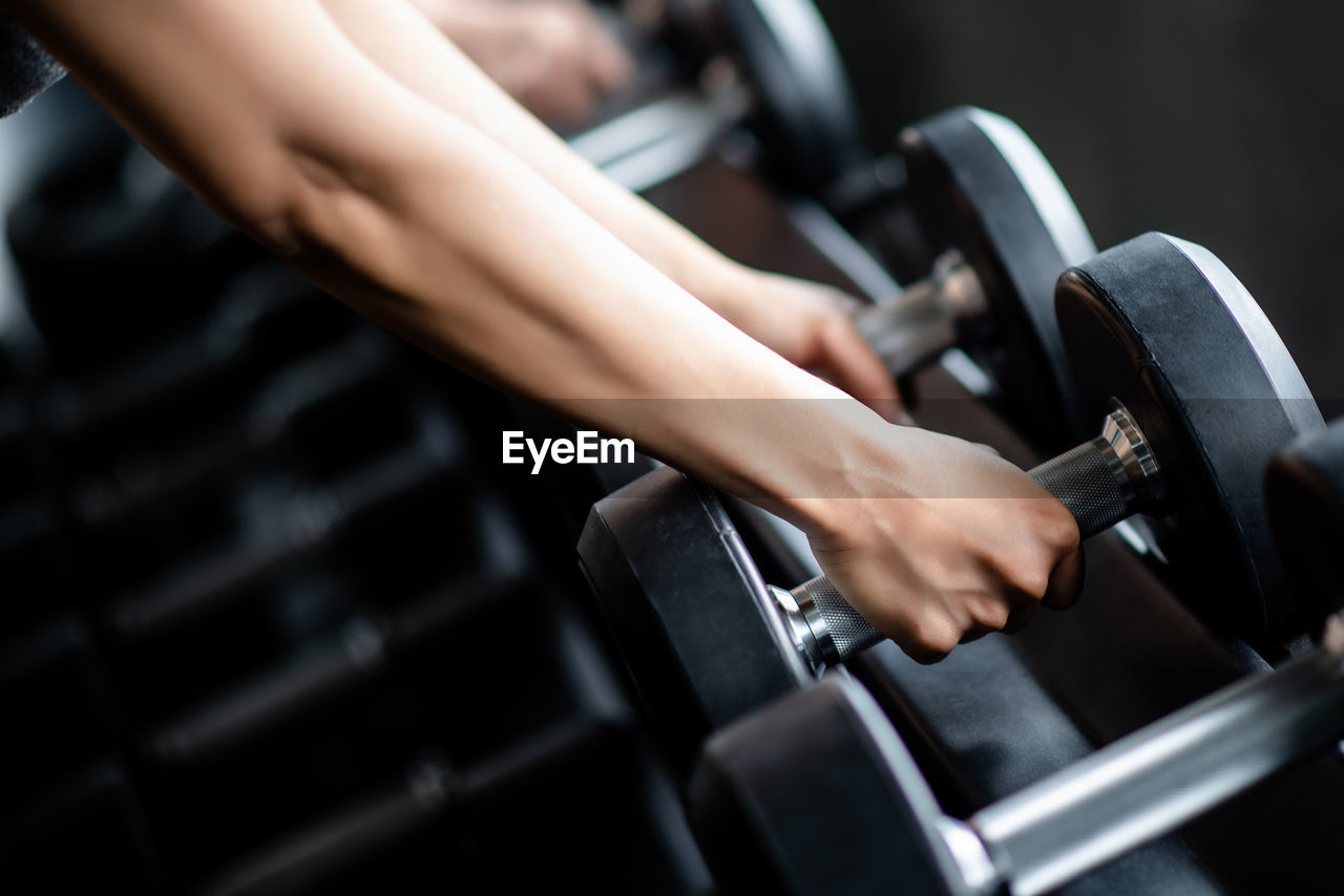 Cropped hands of woman holding dumbbells