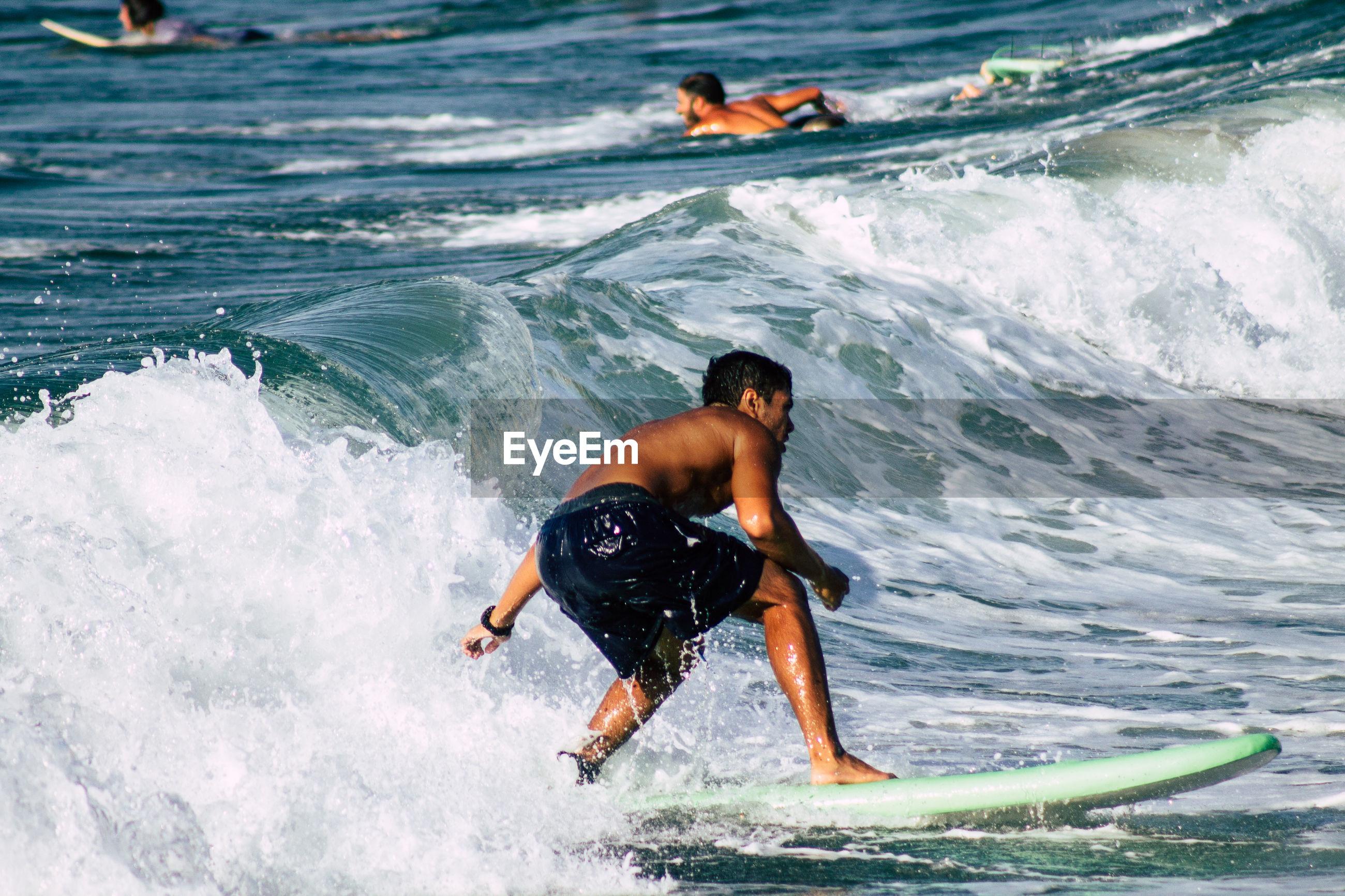 REAR VIEW OF SHIRTLESS MEN IN SEA