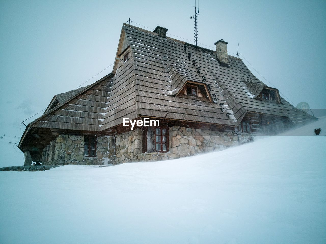 LOW ANGLE VIEW OF SNOW COVERED HOUSE AGAINST SKY