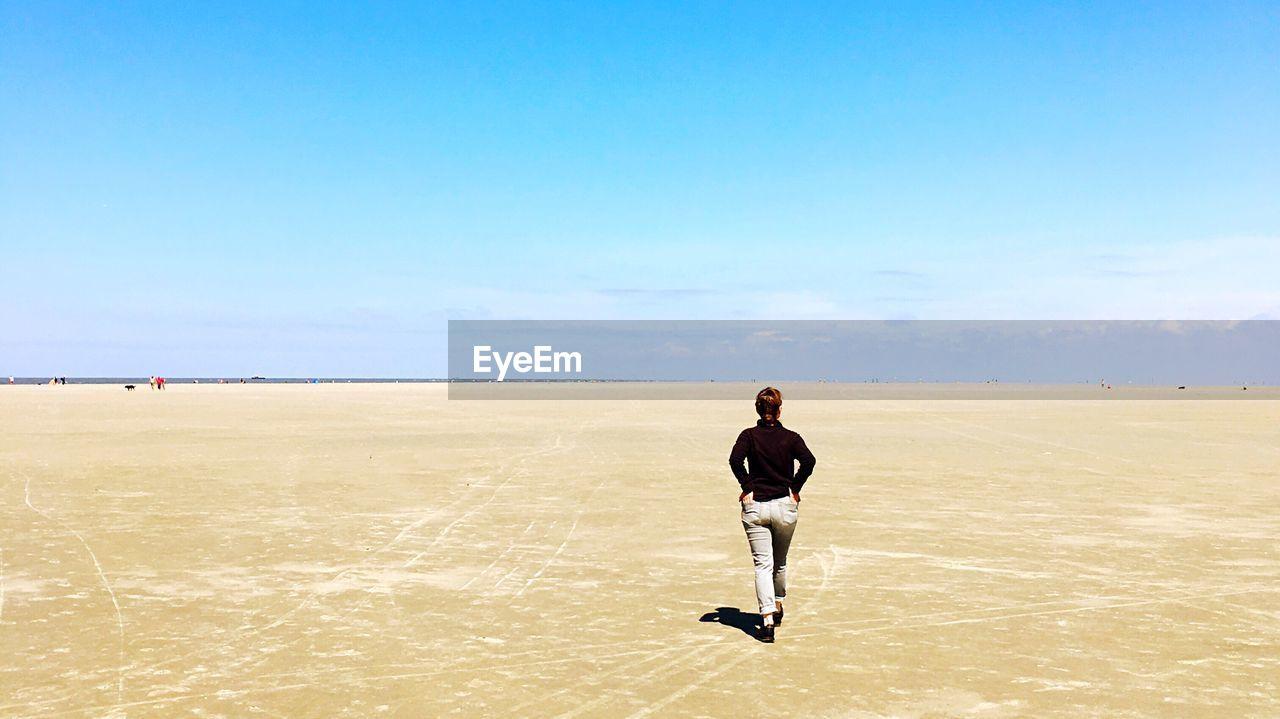 Full Length Rear View Of Woman Walking On Desert Against Blue Sky