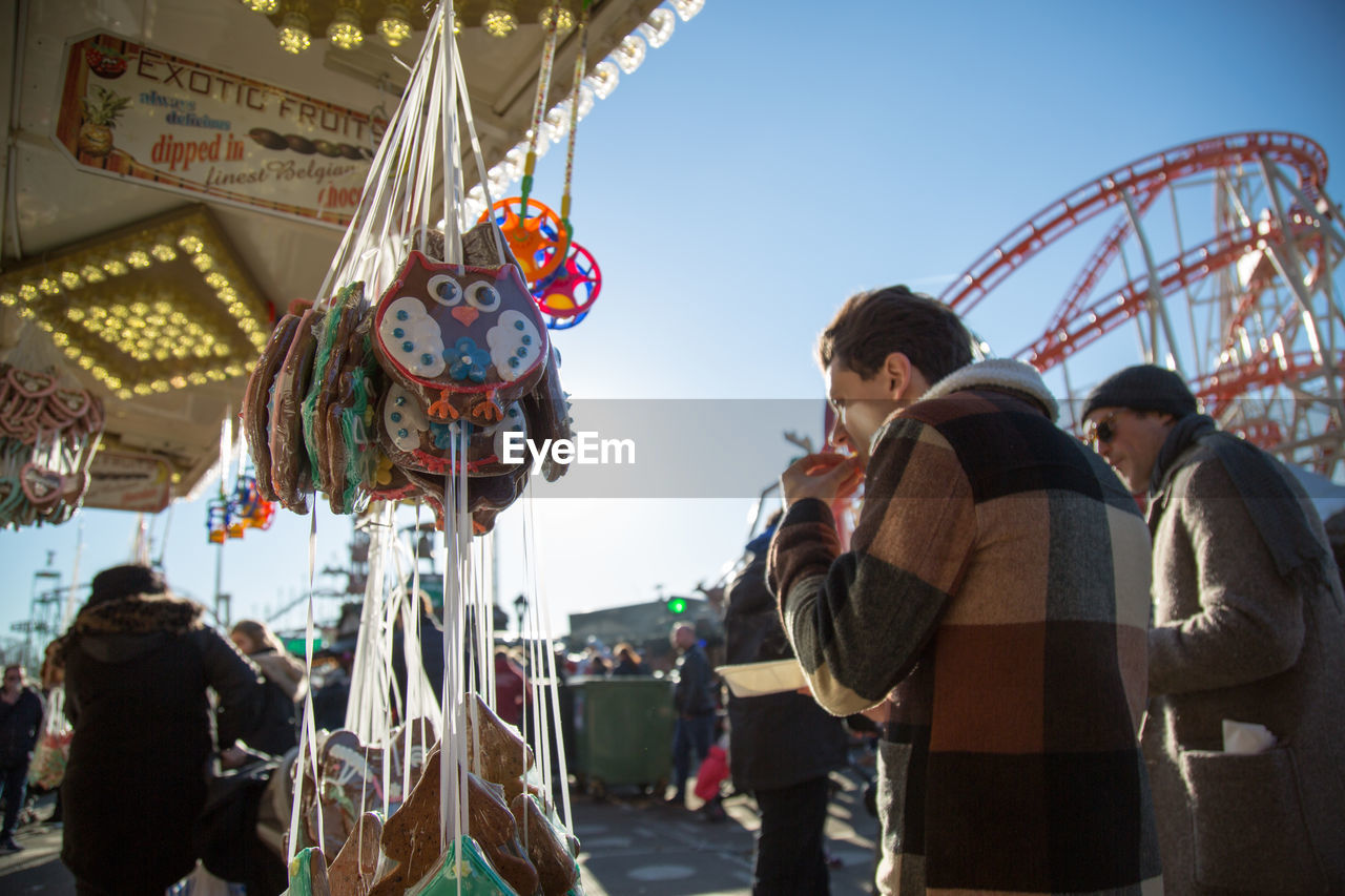 amusement park, amusement park ride, arts culture and entertainment, leisure activity, casual clothing, day, real people, hanging, low angle view, outdoors, built structure, carousel, ferris wheel, men, multi colored, clear sky, sky, young adult, people