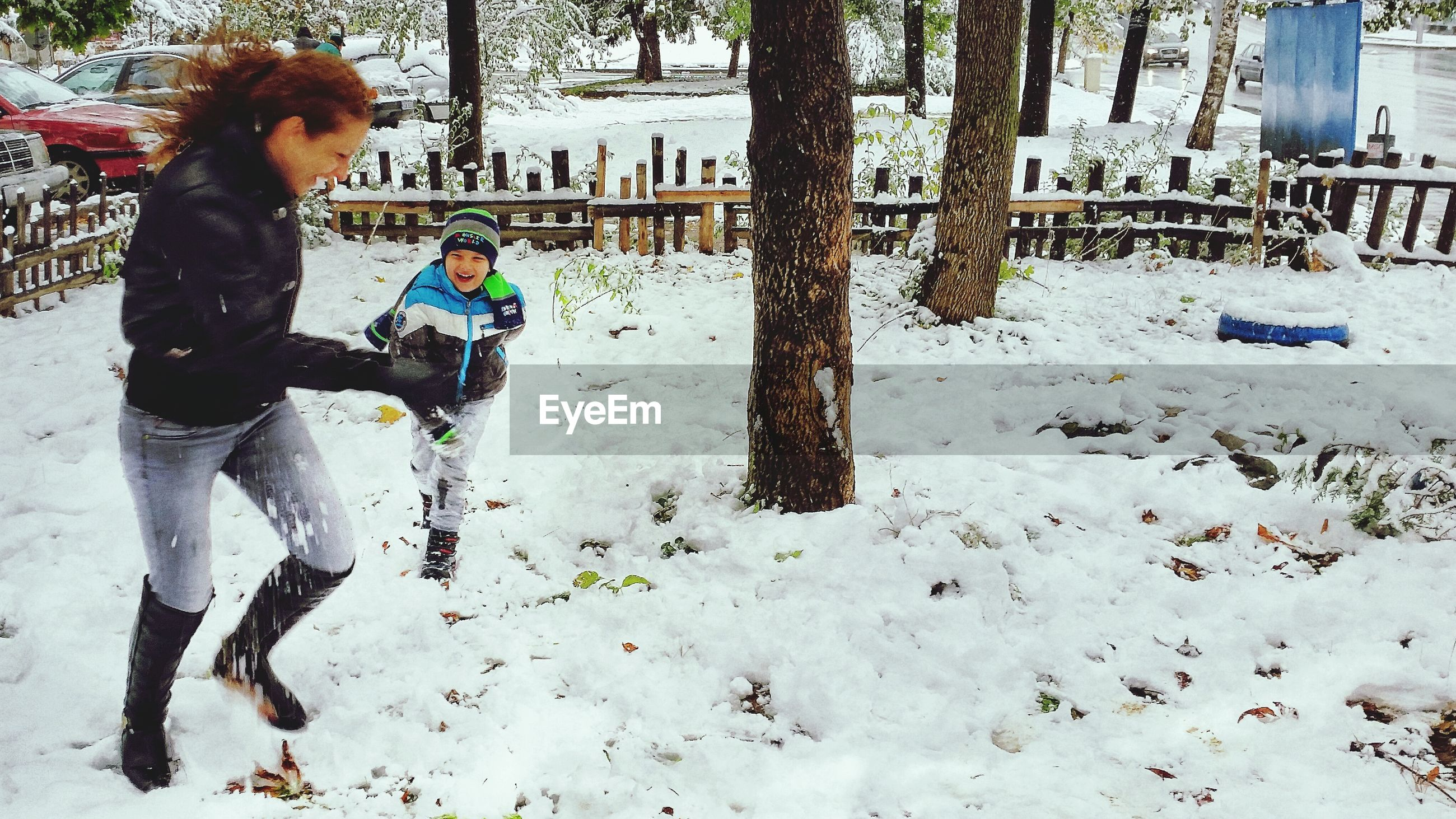 Happy mother and son playing in snow covered park