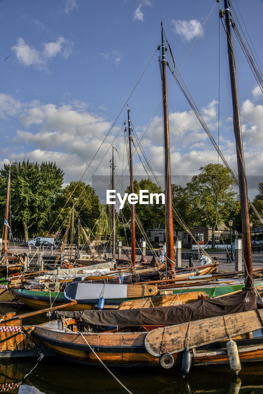 transportation, mode of transportation, sky, nautical vessel, cloud - sky, moored, water, nature, tree, no people, sailboat, day, mast, plant, architecture, pole, outdoors, built structure, harbor, marina