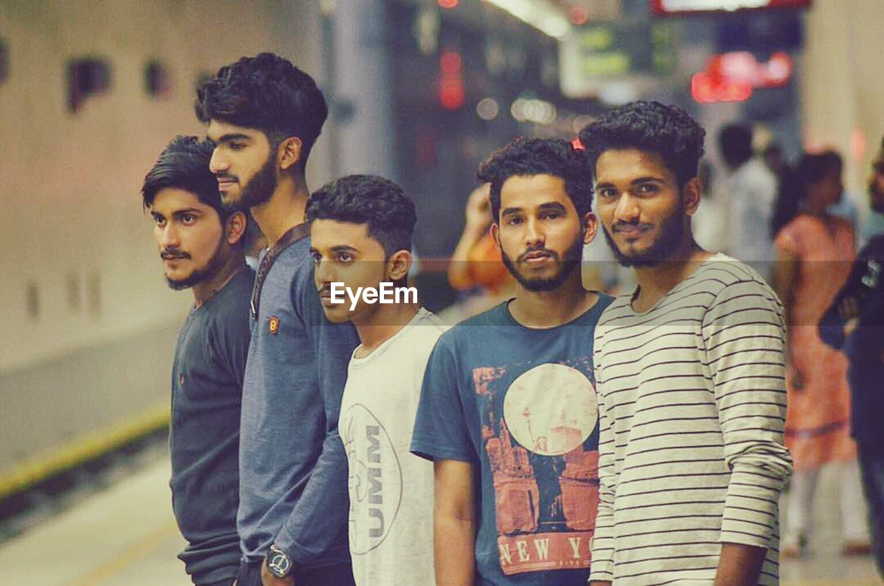 friendship, casual clothing, young adult, lifestyles, youth culture, city, street, city life, young men, togetherness, cool attitude, men, night, cheerful, standing, outdoors, happiness, smiling, adult, portrait, group of people, wireless technology, people, social gathering, modern, only men, adults only, young women, popular music concert