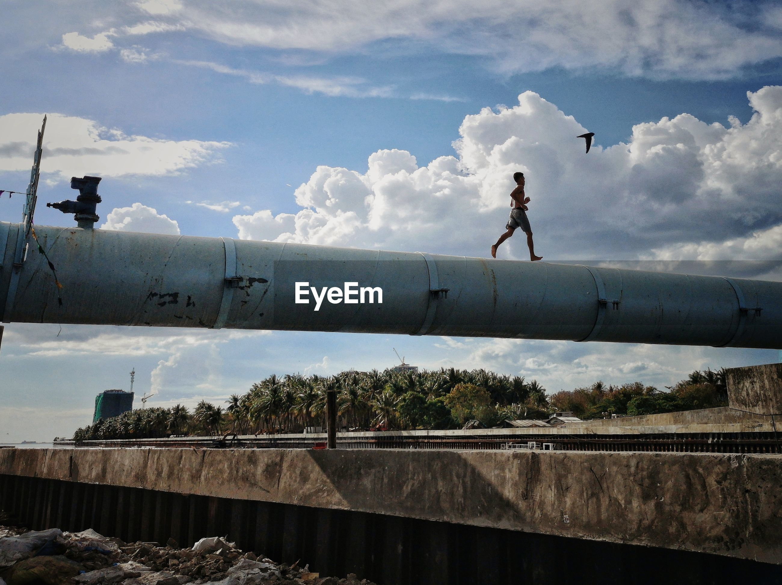 MAN STANDING ON PIPE AGAINST SKY