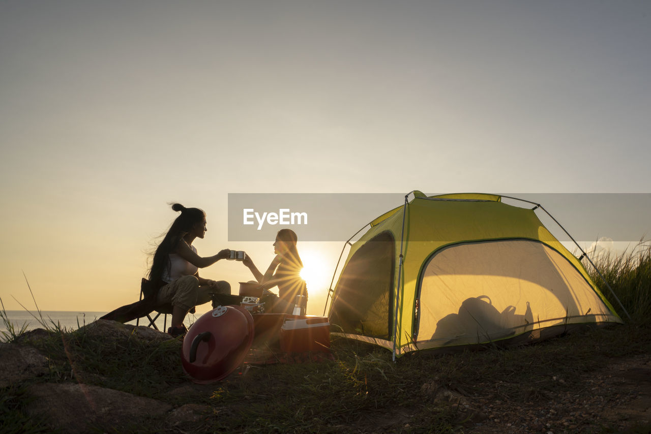 Friends toasting coffee cups by tent against sky during sunset