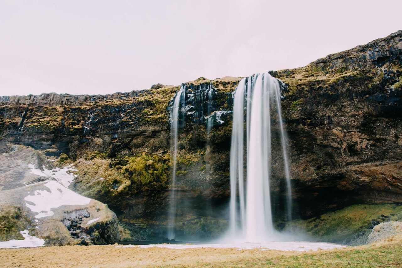 Low Angle View Of Waterfall Along Rocks
