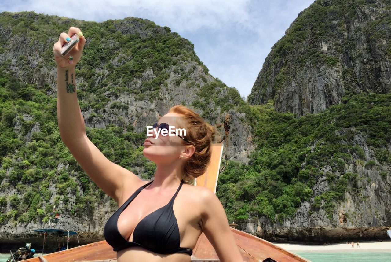 Young woman in longtail boat against rocky mountains taking selfie at phi phi islands
