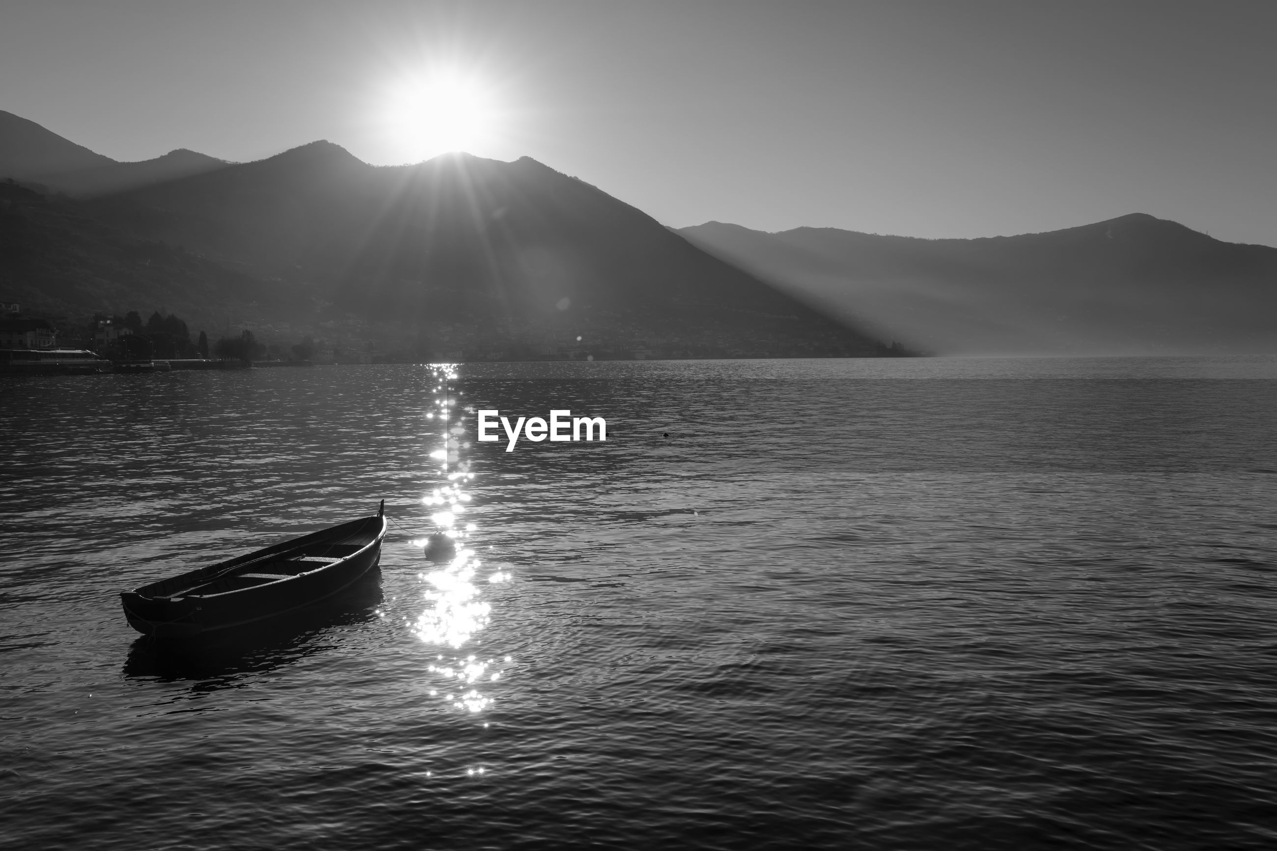 Boat moored in lake against mountains on sunny day