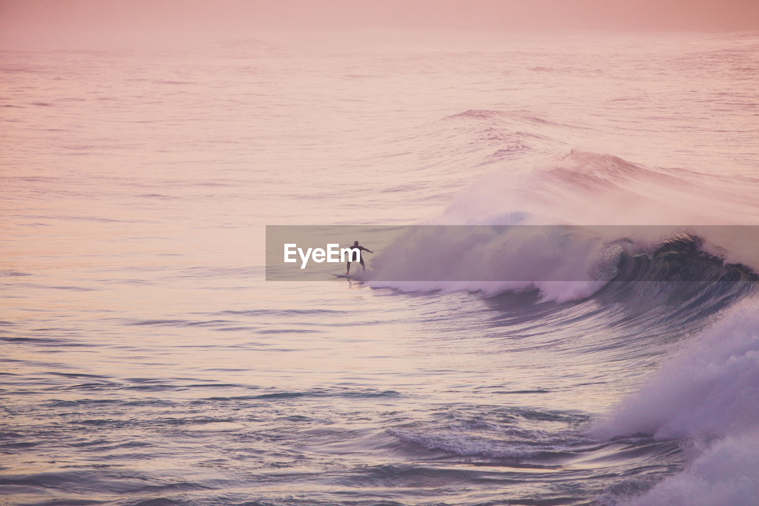 High angle view of man surfing in sea during sunset