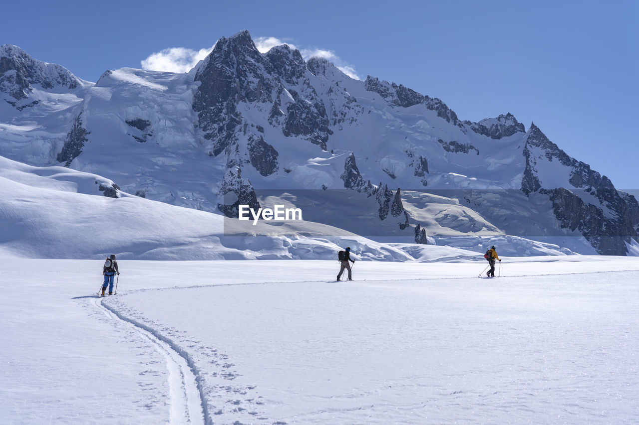People walking on snow against snow capped mountain and sky