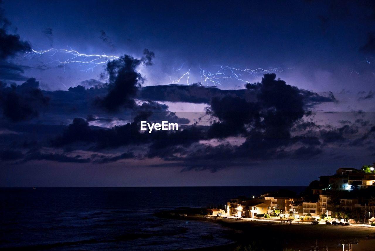 Lightning Over Sea By Illuminated Buildings At Night