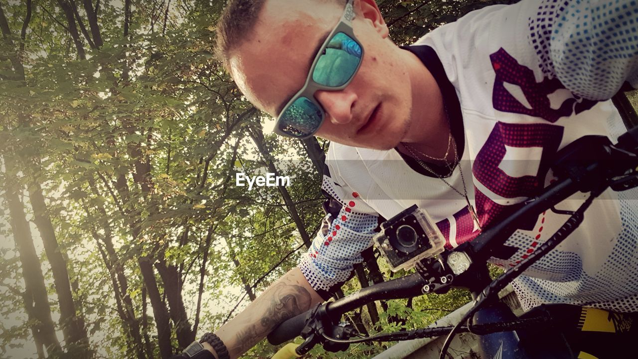 real people, tree, plant, leisure activity, lifestyles, bicycle, casual clothing, men, one person, day, nature, young adult, young men, outdoors, childhood, front view, land, transportation
